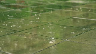 Raindrops falling on the pavement, slow motion shot