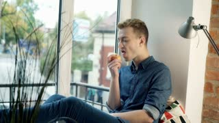 Red haired man eating apple and smiling to the camera by the window