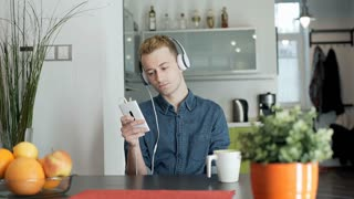 Red haired man relaxing in his house and listening music on headphones