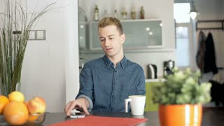 Red haired man sitting at home by the table and browsing internet on smartphone