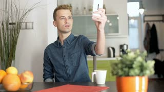 Red haired man sitting at home by the table and doing selfies on smartphone