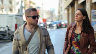 Relationship difficulties: arguing couple walking along the street