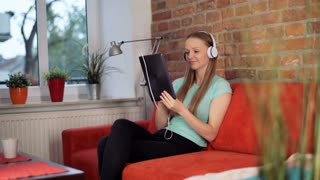 Relaxed girl listening music on headphones while sitting on the sofa