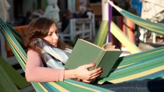 Relaxed girl wearing scarf because of coolness and reading book on hammock