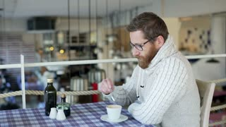 Relaxed man sitting in the restaurant and drinking coffee
