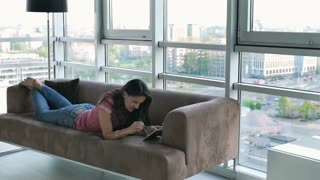Relaxed woman lying on the sofa and using smartphone