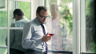 Sad businessman drinking wine next to the window
