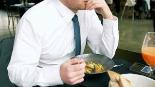 Sad businessman sitting in the restaurant and playing with soup, steadycam shot