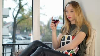 Sad girl drinking wine by the window and looking to the camera
