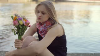 Sad girl sitting next to the water and holding bunch of flowers