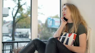 Sad girl talking on cellphone while sitting by the window