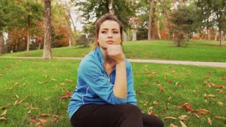 Sad jogger sitting on the grass in the park, steadycam shot