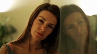 Sad woman looking to camera and face reflection on mirror.