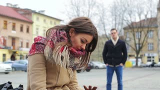 Sad woman sitting on square after quarrel and man looking at her