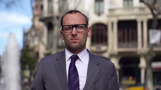 serious businessman looking at camera in front of fountain, slow motion