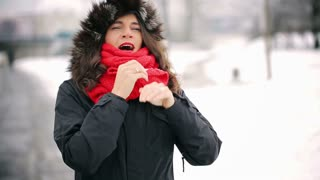 Sick woman blowing nose in the park at winter time