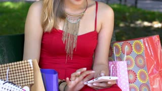 Skinny girl in red dress sitting in the bench and texting on smartphone