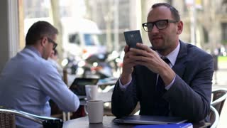 smiled man using his cellphone and sitting outside the cafe, slow motion