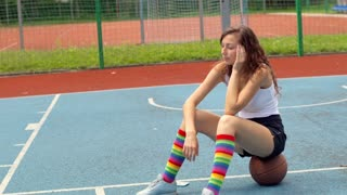 Sport girl sitting on the ball and having painful headache
