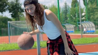 Sporty girl playing basketball on the sports field and smiling to the camera