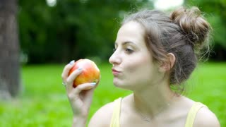 Sporty girl sitting in the park and eating tasty apple