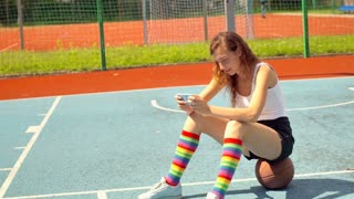 Sporty girl sitting on the ball and typing messages on smartphone