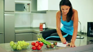 Sporty woman sitting in the kitchen and reading gossip magazine, steadycam shot