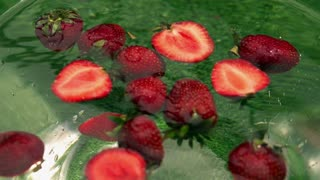 Strawberries spinning in the water, closeup, slow motion shot