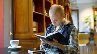 Student answers cellphone while reading book in the library