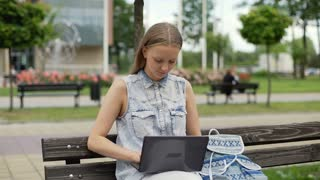 Student answers her cellphone while studying on laptop
