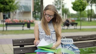 Student doing homework while sitting on the bench and looking to the camera