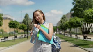 Student drinking water on pathway and smiling to the camera