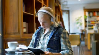 Student reading book and wearing headphones while sitting in the library