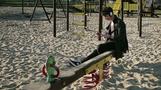 Student sitting on seesaw on playground and listening music