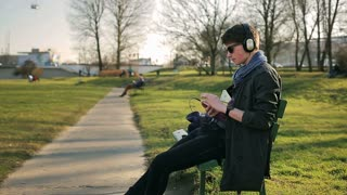 Student sitting on the bench in park and listening music on headphones