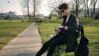 Student sitting on the bench in park and texting on smartphone