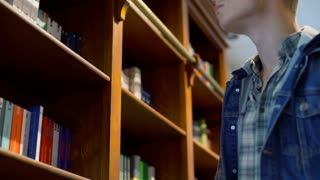 Student standing next to bookshelves and looking for a book