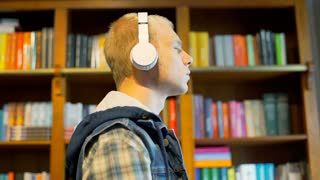 Student standing next to the bookshelves and listening music on headphones