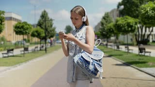 Student standing with blue backpack and listening music on pathway