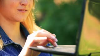 Student using tablet in the park and smiling to the camera, steadycam shot