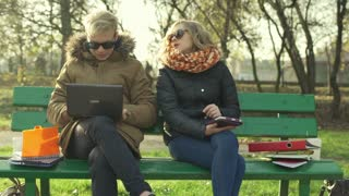 Students sitting on the bench in the park and using modern technology