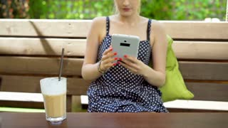 Stylish girl browsing internet on tablet and drinking frappe while sitting on th