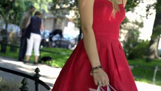 Stylish girl going round and holding shopping bags, slow motion shot