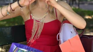 Stylish girl putting golden necklace on herself, slow motion shot