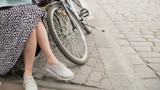 Stylish girl sitting next to her bicycle and reading a book, steadycam shot