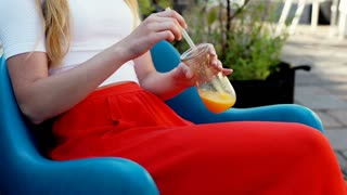 Stylish girl sitting on comfy chair in the outdoor cafe and holding orange juice