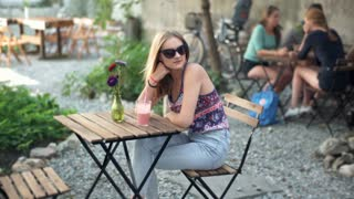 Stylish girl wearing sunglasses and sitting by the wooden table in outdoor cafe