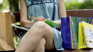 Stylish girl writing something in her notebook and sitting on the bench