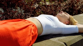 Stylish, skinny girl sleeping in public place at sunny day