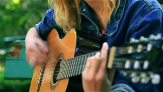 Teeange girl playing on the guitar in the park, steadycam shot